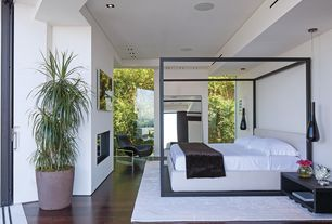 Modern Master Bedroom with Maxalto Alcova Bedframe, Hardwood floors, Series 3300 Armchair, French doors, Pendant light