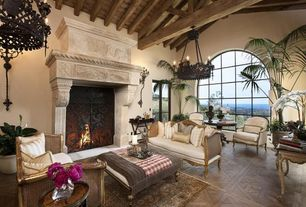 Mediterranean Living Room with Wall sconce, Fireplace, Chandelier, French doors, metal fireplace, Cathedral ceiling