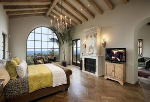 Mediterranean Master Bedroom with Arched window, metal fireplace, stone fireplace, Chevron wood floor pattern, Wall sconce