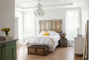 Eclectic Guest Bedroom with Antique dresser, Laminate floors, Chandelier, Standard height, Steamer trunk, specialty window