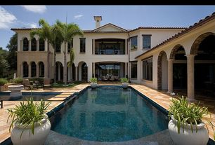 Mediterranean Swimming Pool with French doors, Deck Railing, Raised beds, Arched window, Lap pool, exterior stone floors