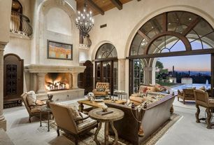 Traditional Living Room with Crown molding, Exposed beam, Fireplace, Balcony, Cantera stone fireplace surround, Chandelier
