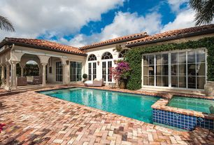Mediterranean Swimming Pool with Transom window, Pool with hot tub, French doors, exterior brick floors