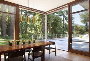 Contemporary Dining Room with Pendant light, Hardwood floors, sliding glass door, Standard height, picture window