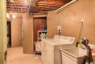 Craftsman Laundry Room with Exposed beam, sandstone tile floors, flush light, Built-in bookshelf