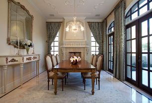 Traditional Dining Room with French doors, Chandelier, Cement fireplace, Crown molding, Arched window