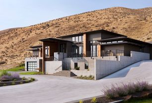 Modern Exterior of Home with picture window, French doors, exterior stone floors, Raised beds, Deck Railing, Casement