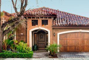 Mediterranean Exterior of Home with exterior brick floors, exterior concrete tile floors, Pathway, Barn door, six panel door