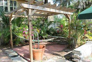 Tropical Patio with Raised beds, exterior terracotta tile floors, Trellis, exterior tile floors, double-hung window, Fence