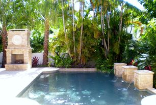 Tropical Swimming Pool with Water feature, Exterior fireplace, Tropical plantings, Fence, exterior stone floors
