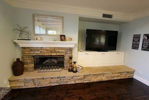 Rustic Living Room with stone fireplace, Crown molding, Hardwood floors, Built-in bookshelf
