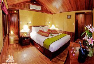 Tropical Guest Bedroom with interior wallpaper, specialty door, Hardwood floors, Wainscotting, High ceiling, Exposed beam