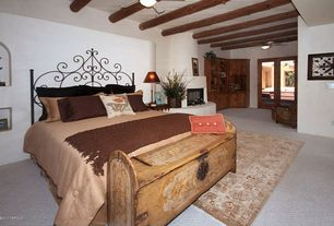 Mediterranean Guest Bedroom with flush light, Cement fireplace, Ceiling fan, Carpet, French doors, Exposed beam