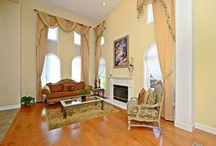 Traditional Living Room with can lights, Fireplace, Hardwood floors, Cement fireplace, High ceiling, Arched window