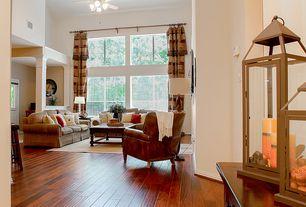 Traditional room with Columns, Glass panel door, Chandelier, Hardwood floors, Ceiling fan