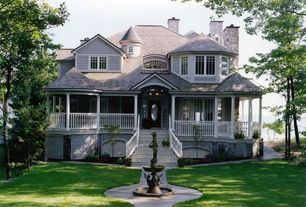 Traditional Exterior of Home with Glass panel door, Iron garden fountain, Deck Railing, Covered porch, specialty window