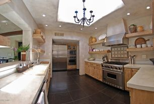 Mediterranean Kitchen with Wall Hood, wall oven, Chandelier, Limestone counters, Limestone, Framed Partial Panel, U-shaped