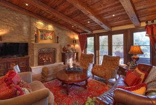 Eclectic Living Room with Exposed beam, Hardwood floors, Built-in bookshelf, High ceiling, stone fireplace, French doors