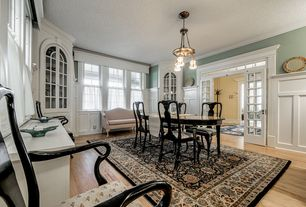 Traditional Dining Room with Built-in bookshelf, Crown molding, French doors, double-hung window, Wainscotting, Chandelier
