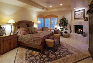 Traditional Guest Bedroom with High ceiling, Arched window, Ceiling fan, Black traditional design area rug, Cement fireplace