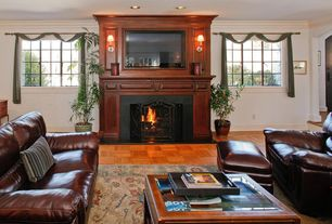 Traditional Living Room with Leather recliner, Parquet Floor, Hardwood floors, Leather sofa, Wall sconce, Cream and green rug