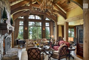Rustic Great Room with stone fireplace, Columns, Cathedral ceiling, Hardwood floors, Exposed beam, Chandelier, flush light