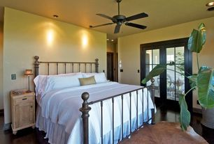 Country Master Bedroom with Built-in bookshelf, French doors, Ceiling fan, Concrete floors