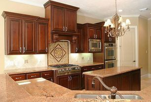 Traditional Kitchen with Concrete floors, can lights, U-shaped, full backsplash, Kitchen island, Custom hood, six panel door