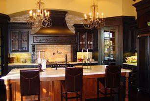 Mediterranean Kitchen with Custom hood, Paint 1, L-shaped, Glass panel, Kitchen island, Limestone Tile, Chandelier, gas range