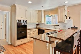 Traditional Kitchen with Recessed lighting, Light hardwood floors, Raised panel, Crown molding, Pendant light, Breakfast bar