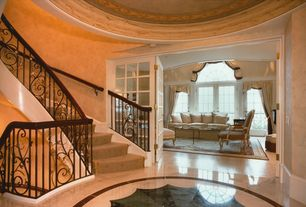 Traditional Entryway with stone tile floors, curved staircase, specialty tile floors, French doors, Ceiling cove lighting