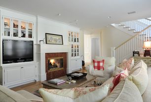 Traditional Living Room with stone fireplace, Hardwood floors, Fireplace, can lights, Built-in bookshelf, Standard height