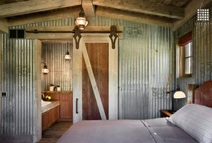 Rustic Guest Bedroom with Duvet, Pendant light, Exposed beam, Standard height, Casement, Barn door, Hardwood floors