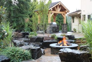 Rustic Landscape/Yard with exterior stone floors, Outdoor gas fire pit with logs, Glass panel door, Paint, Outdoor kitchen