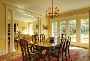 Traditional Dining Room with Crown molding, Columns, Chair rail, interior wallpaper, Chandelier, French doors