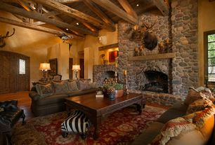 Rustic Living Room with Eldorado Stone River Rock - Colorado, Built-in bookshelf, Hardwood floors, stone fireplace