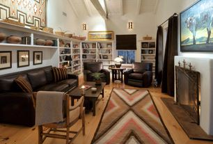 Eclectic Living Room with Wall sconce, Built-in bookshelf, Fireplace, Cathedral ceiling, Hardwood floors, Cement fireplace