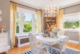 Cottage Dining Room with Built-in bookshelf, Aspen Rectangular Pedestal Table, Crown molding, Window seat, Olin Area Rug