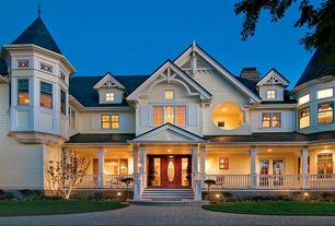 Traditional Exterior of Home with Exterior lighting, Turret, Wood shutters, Columns, Stained glass window, Bay window