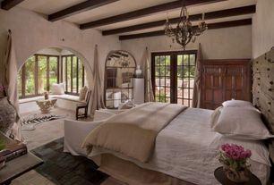 Eclectic Master Bedroom with Exposed beam, French doors, Window seat, Carpet, Chandelier