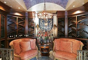 Traditional Wine Cellar with Built-in bookshelf, slate floors, Chandelier