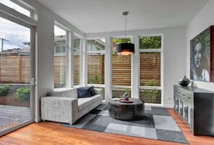 Contemporary Living Room with Laminate floors, Transom window, Pendant light