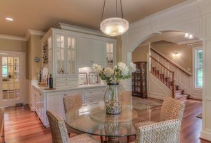 Traditional Dining Room with Laminate floors, Standard height, can lights, Crown molding, Pendant light