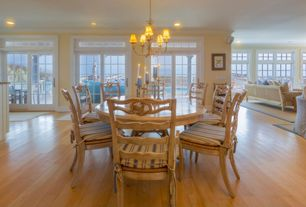 Cottage Dining Room with Chandelier, Transom window, Hardwood floors, Crown molding