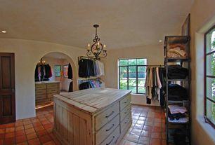 Mediterranean Closet with can lights, Casement, Chandelier, terracotta tile floors, specialty door, Standard height