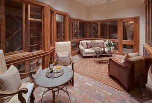 Traditional Wine Cellar with Built-in bookshelf, Stone table top, Glass panel door, Area rug, Built in storage, Brick floors
