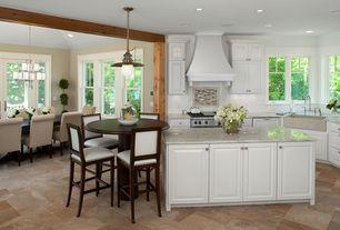 Modern Kitchen with Framed Partial Panel, Kitchen island, can lights, gas range, Custom hood, L-shaped, Pendant light