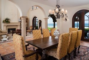 Mediterranean Dining Room with French doors, Standard height, Columns, slate floors, Chandelier, Wall sconce