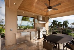 Tropical Patio with Outdoor kitchen, exterior stone floors, Deck Railing