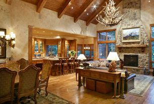 Country Great Room with Wall sconce, Exposed beam, Built-in bookshelf, Cathedral ceiling, Hardwood floors, Casement